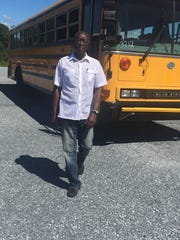 Charles Kyeremeh Sr. stands in front of bus that he will deliver to a grade school in his native country of Ghana.