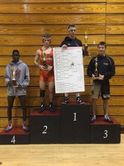 Lely 132-pounder Josh Sheldon stands atop the podium with his trophy and bracket after winning his weight class at the Santaluces Holiday Wrestling Tournament on Saturday, Dec. 10.