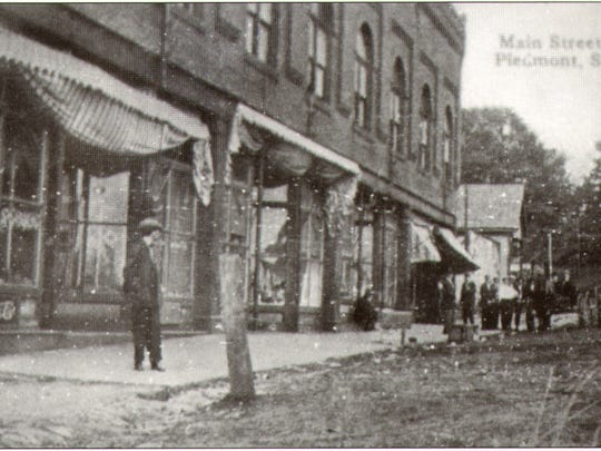 A man stands along Main Street in downtown Piedmont in this 1905 postcard.
