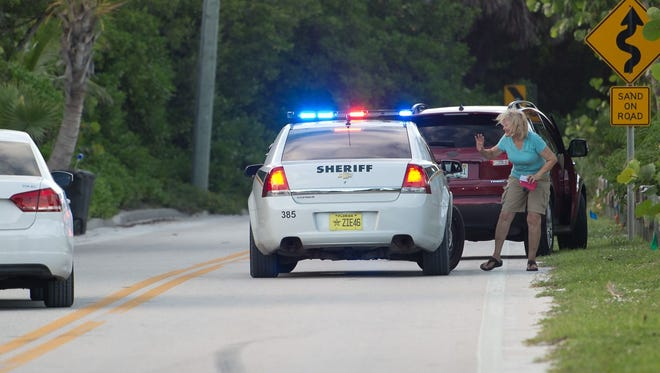 A Martin County Sheriff's Office deputy checks on a stopped motorist on Southeast MacArthur Boulevard on Wednesday as residents in Martin County prepare for Hurricane Matthew. The barrier islands were given an evacuation notice earlier in the day.
