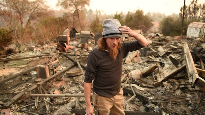Ryan Spainhower reacts while talking about his burned home in Paradise, California on November 18, 2018.