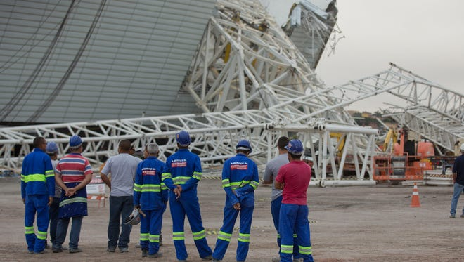 Construction workers pause in front of the damage caused by the collapse at the Arena Corinthians.
