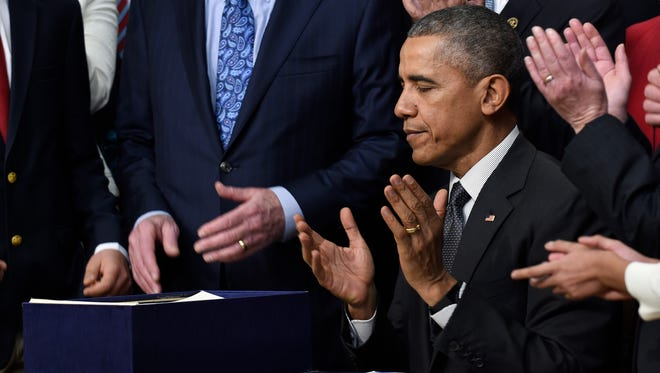 """President Barack Obama applauds after signing the """"Every Student Succeeds Act,"""" a major education law setting U.S. public schools on a new course of accountability, Thursday, Dec. 10, 2015, in Washington. The law will change the way teachers are evaluated and how the poorest performing schools are pushed to improve. (AP Photo/Susan Walsh)"""