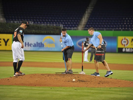 Miami Marlins manager of grounds Greg Jones, center,