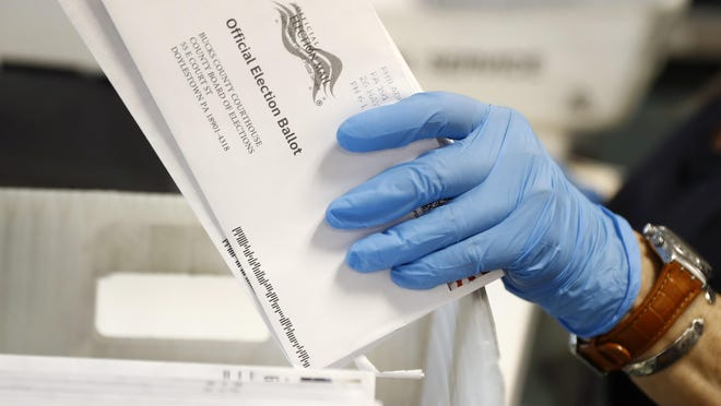 FILE - In this May 27, 2020 file photo, a worker processes mail-in ballots at the Bucks County Board of Elections office prior to the primary election in Doylestown, Pa. Deep-pocketed and often anonymous donors are pouring over $100 million into an intensifying dispute about whether it should be easier to vote by mail, a fight that could determine President Donald Trump's fate in the November election. (AP Photo/Matt Slocum, File)