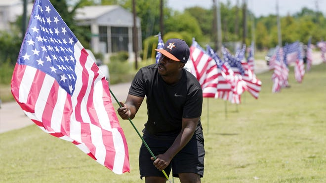 Bryan Smart plants American flags along Hillcroft Ave. as he walks toward The Fountain of Praise church Sunday, June 7, 2020, in Houston. A public memorial and private funeral service for George Floyd will be held at the church. Floyd died after being restrained by Minneapolis Police officers on Memorial Day. (AP Photo/David J. Phillip