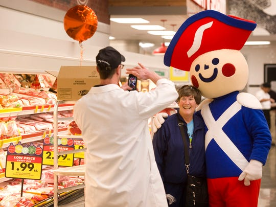 Colleen McLaughlin of Evansville, center, has a portrait made by Chad Mayes, asst. meat manager, with Henry, the Schnucks mascot, during the grand opening of the new Schnucks supermarket at Lawndale Commons Wednesday morning.