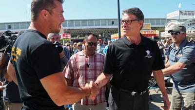 "Republican Rick Perry shakes hands with ""The Bachelorette"" contestant Chris Soules, an Iowa farmer who was judging a barbecue contest at the Iowa State Fair on Aug. 13."