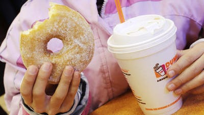 In this file photo, a girl holds a doughnut and a beverage at a Dunkin' Donuts in New York. Dunkin? Brands CEO Nigel Travis said in a phone interview Thursday that the company is pushing to get its cashiers to ?upsell? to afternoon customers. It?s part of an effort to increase sales after stores have emptied out after the morning rush.