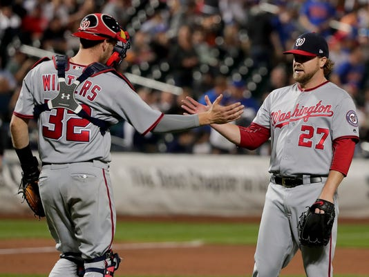 Washington Nationals catcher Matt Wieters (32) and pitcher Shawn Kelley (27) shake hands after they defeated the New York Mets in a baseball game, Friday, June 16, 2017, in New York. (AP Photo/Julie Jacobson)