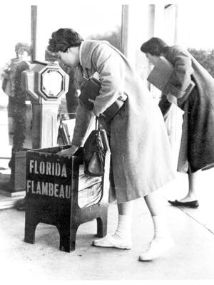 Students pick of copies of the Florida Flambeau in 1960. January 23 marks the publication's 100th anniversary.