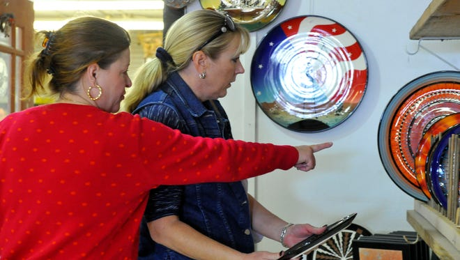 Kimberly Francis and Rebecca Hopkins examine pottery by Roger Allen while shopping for gifts during the Thanksgiving Open House at the Chicken Farm Art Center in 2014.