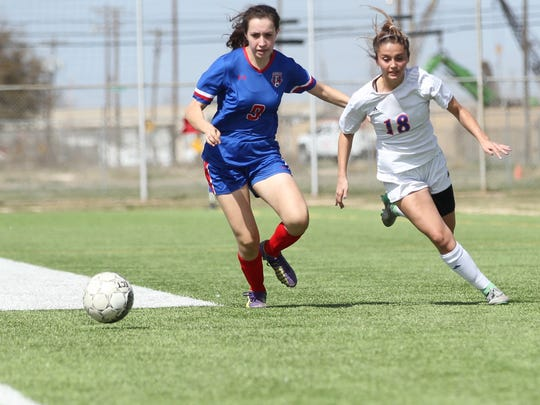 San Angelo Central High School's Addison Bonaventure (right) and a Waco Midway player fight for a loose ball during the District 8-6A soccer finale at Old Bobcat Stadium on Tuesday, March 13, 2018. The teams tied 0-0, but the Lady Cats had already secured the district crown.