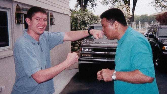 Port Clinton graduate Jack Gibson shows Muhammad Ali his left hand.