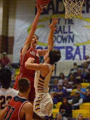 Jim Ned's Harrison Renner puts up a shot in the lane over Merkel's Jordan Cardenas while Ned's Dylan Bryant (33) and MHS' Jonah White (23) position themselves for a rebound in the third quarter of Friday's game in Merkel.