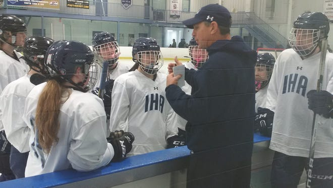 Immaculate Heart girls hockey players listen as coach Doug Brown gives instructions during a time out Sunday versus Oak Knoll at Ice Vault.