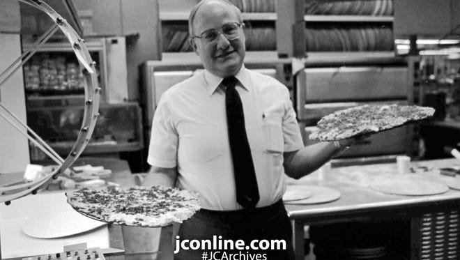 Arni Cohen, owner of Arni's, shows off two of his famous pies. Photo taken Feb. 16, 1983.