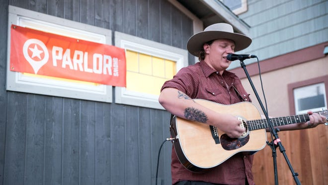Jake Houston plays the guitar and sings honky-tonk music in Doug and Bin Bin Erwin's backyard for an intimate Parlor Show Aug. 26, 2016.