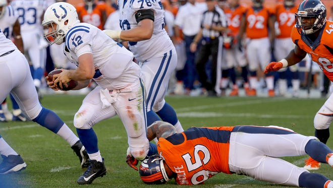 Indianapolis Colts quarterback Andrew Luck (12) is tripped up by Denver Broncos defensive end Derek Wolfe (95) late in the fourth quarter at Sports Authority Field at Mile High in Denver on Sunday, September 18, 2016.