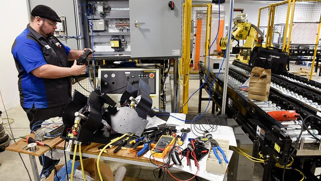 Luis Maldonado, an automation technician at Central McGowan, works on a new robotic unit Tuesday, Sept. 20, in St. Cloud.