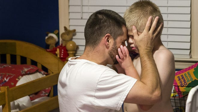 Carl Kapes holds his son Brayden's head in his hands, pressing their foreheads together, after Brayden reached out to grab his face before bedtime.