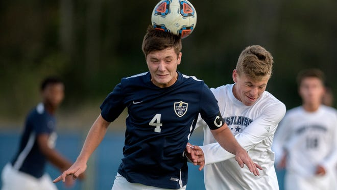 DeWitt's Evan Greisinger, left, heads the ball as East Lansing's Will Knapp, right, closes in during the first half on Monday, Oct. 16, 2017, at Archer Stadium in East Lansing.