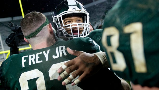 Michigan State senior Gerald Holmes, right, hugs fellow senior teammate Chris Frey after the game on Saturday, November 18, 2017, at Spartan Stadium in East Lansing. The Spartans won 17-7.