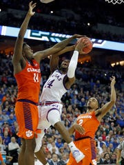 Kansas' Malik Newman, center, has his shot blocked by Clemson's Elijah Thomas, left, while Marcquise Reed, right, watches during the second half of a regional semifinal game in the NCAA men's college basketball tournament Friday, March 23, 2018, in Omaha, Neb. (AP Photo/Charlie Neibergall)