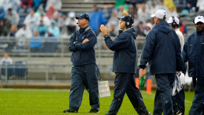 Penn State head football coach James Franklin, left, stands on the field with his staff after calling a timeout during a win against Buffalo in the season opener in 2015.