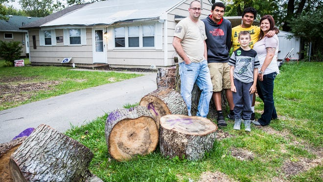 Central player Nikko Morris and his family stands outside of their home in Muncie Wednesday evening. A tree in the property's front yard fell during a storm and crashed through the home's roof.  They've been staying in a hotel for the last six weeks while damage to the house is repaired.