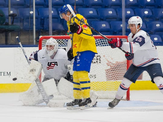 USA White goalie Dylan St. Cyr (30), of Northville, gets set for a shot Sunday. Sparring in front of the net are Sweden's Isac Lundestrom (29) and USA White's David Farrance (25).