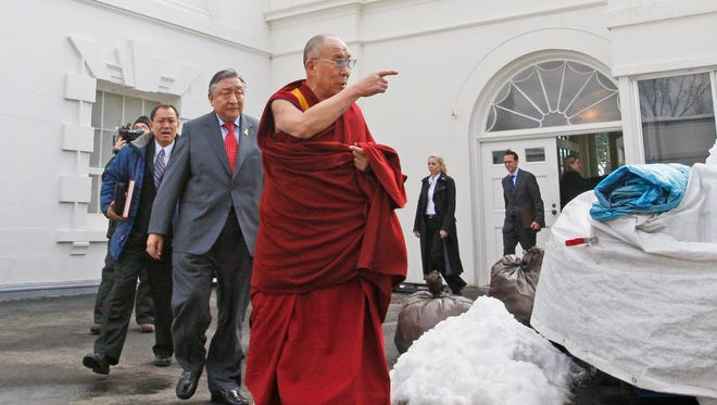 The Dalai Lama walks out of the White House on Feb. 18, 2010, after meeting with President Obama.