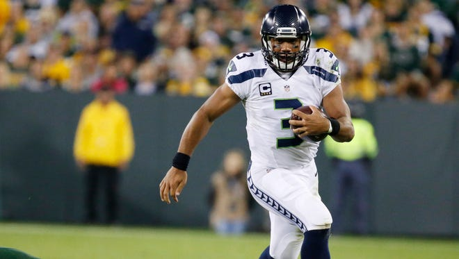 Seattle Seahawks' Russell Wilson runs past Green Bay Packers' Nick Perry during the second half of an NFL football game Sunday, Sept. 20, 2015, in Green Bay, Wis.