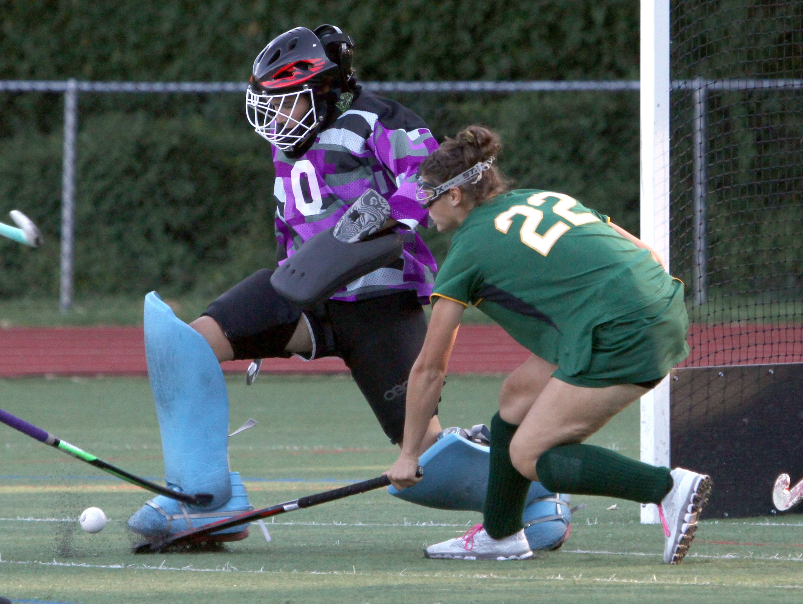 Rye goalie Maggie Devlin makes a kick save while being pressured by Lakeland's Cameron Lischinsky during a varsity field hockey game at Rye High School Sept. 15, 2016. Lakeland defeated Rye 3-1.
