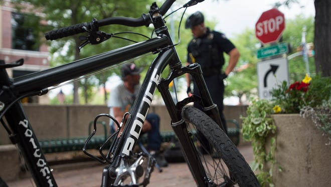 Fort Collins Police Services Officer Matt Hahn talks to a man who was sleeping on a bench during Hahn's patrol of Old Town Wednesday as part of the department's increased bike patrols in the area.