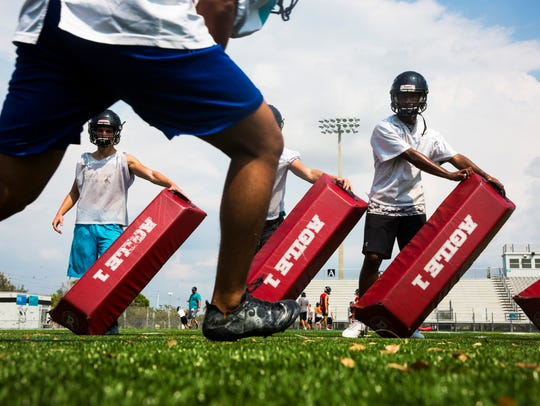 Players run drills during practice at Gulf Coast High