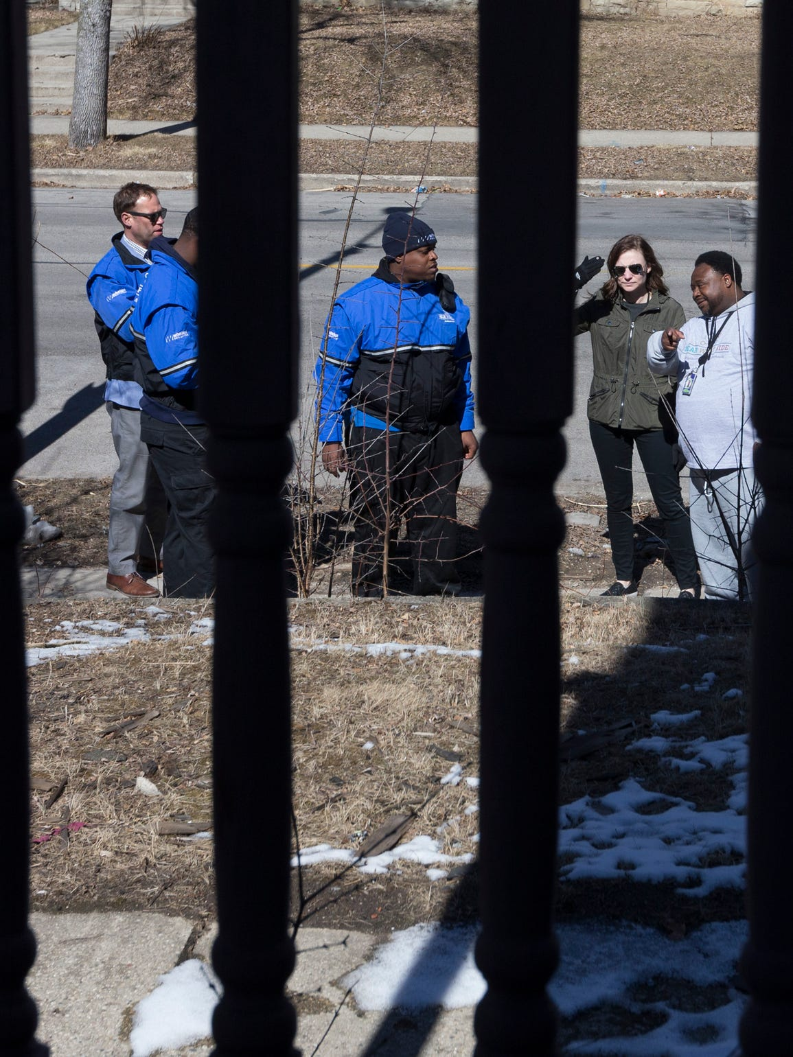"""Assistant district attorney Catelin Ringersma (second from right) and Safe & Sound community prosecution unit coordinator Bobby McQuay Jr. (right) stop at a city-owned vacant house during a """"blight sweep"""" to take note of problems that need to be dealt with March 14 on the near west side of Milwaukee."""