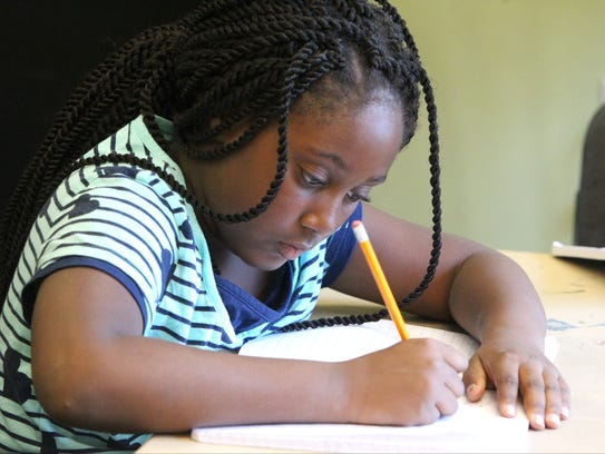 Inara Johnson works on a project during summer camp