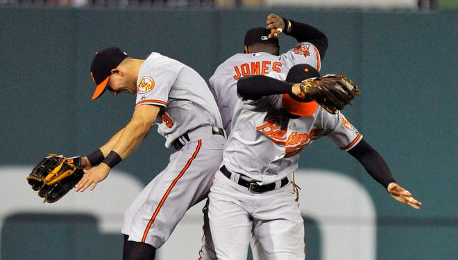 Orioles outfielders David Lough (left), Adam Jones (center) and Nick Markakis (right) celebrate after a game.