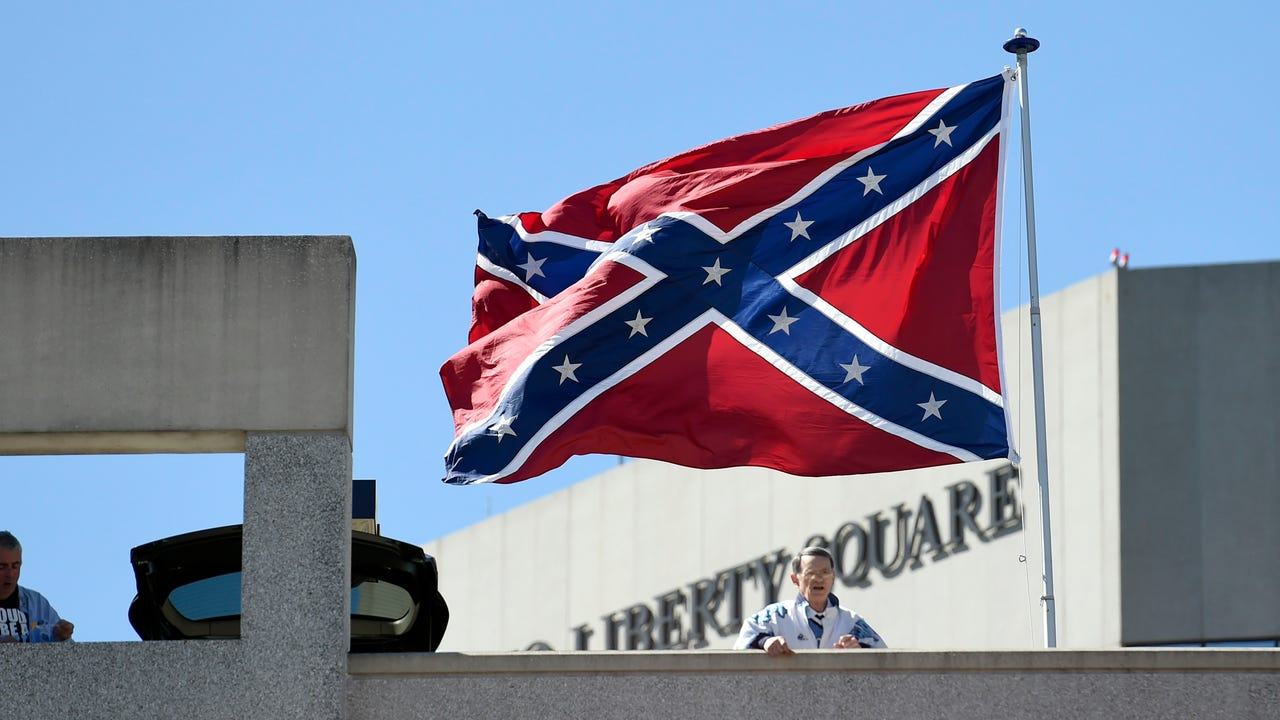 A small group of protesters flew a Confederate flag outside the Greensville, S.C., arena hosting two NCAA tournament games on Sunday.