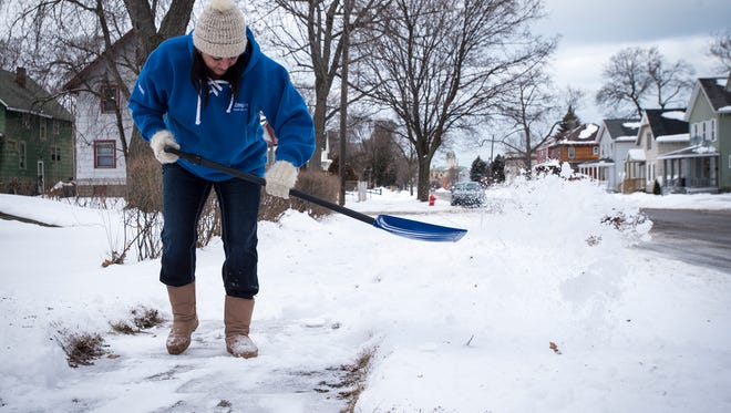 Heidi Nolan shovels the sidewalk in front of her Sixth Street home in Port Huron Tuesday. Monday's snowstorm dropped about 4.5 inches on the area, according to a representative from the National Weather Service.