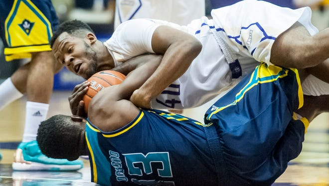 James Madison forward Yohanny Dalembert (40) dives on top of UNC Wilmington center Chuck Ogbodo (13) while chasing down a loose ball during the first half of an NCAA college basketball game in Harrisonburg on Thursday, Jan. 28, 2016.