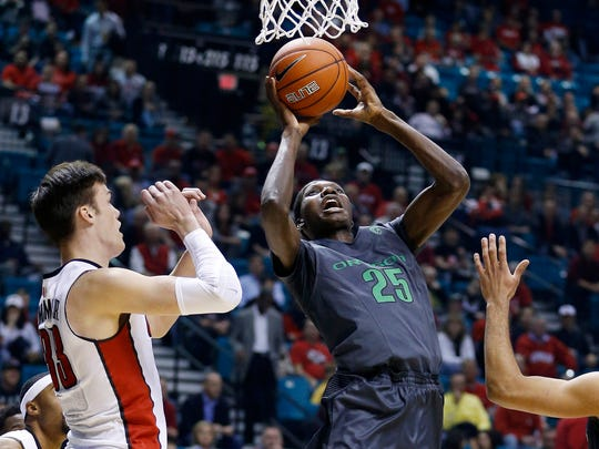 Oregon forward Chris Boucher shoots in front of UNLV forward Stephen Zimmerman Jr., left, during the first half of an NCAA college basketball game Friday, Dec. 4, 2015, in Las Vegas.