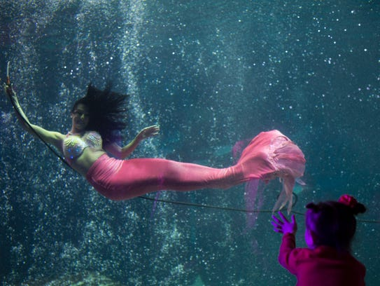 A young girl waves to a 'mermaid' last fall at Adventure Aquarium in Camden. The mermaids return Nov. 5 at the Camden Waterfront.
