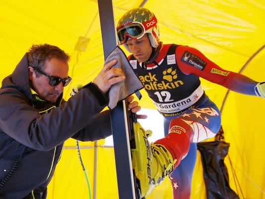 FILE - This Dec. 17, 2015 file photo shows ski technician Leo Mussi working on United States's Steven Nyman skis during a training session for a men's World Cup downhill in Val Gardena, Italy. Technicians preparing Alpine skis are key to Olympic success in a sport where speeds can touch 90 mph (145 kph) and wins are often decided by hundredths of seconds. Still, the crucial craftsmen are almost unknown to most fans, and do much of their best work out of sight in cellar rooms _ waxing and filing skis to give their racer an edge. (AP Photo/Alessandro Trovati, files)
