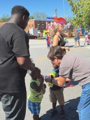 A Poplar Springs Baptist Church member helps a toddler to a bottle of water.
