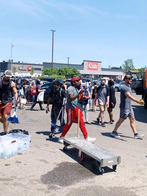 Pierre Paul, with the megaphone at center, directs volunteers cleaning up the looted Lake Street Target store in Minneapolis, Minn. on May 31, 2020.