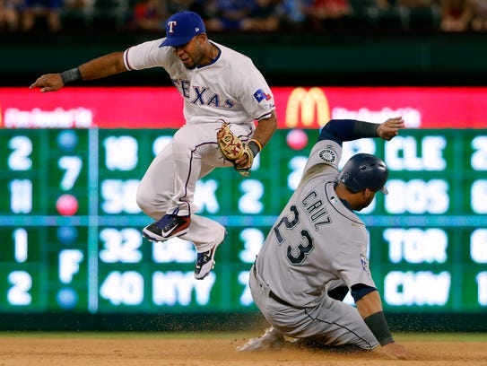 Texas Rangers shortstop Elvis Andrus, top, leaps out