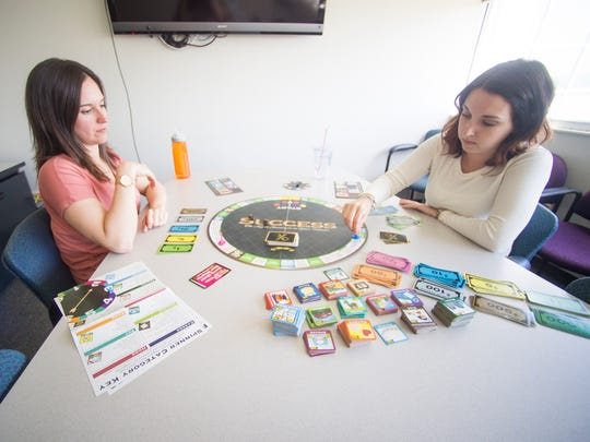 Knoxville Business Journal's Brenna McDermott, left, and Cortney Roark, right, play Success, a board game, on Tuesday, May 1, 2018.