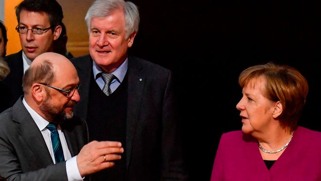 This file photo taken on Feb. 2, 2018 in Berlin shows German Chancellor and leader of the Christian Democratic Union (CDU) Angela Merkel (R), the leader of the Social Democratic Party (SPD) Martin Schulz (L) and the chairman of the Bavarian Christian Social Union (CSU) Horst Seehofer (C) entering the conference room at the headquarters of Social Democrats Party (SPD) for coalition talks to form a new government.